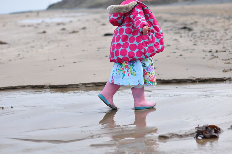 Little L walking in stream on beach
